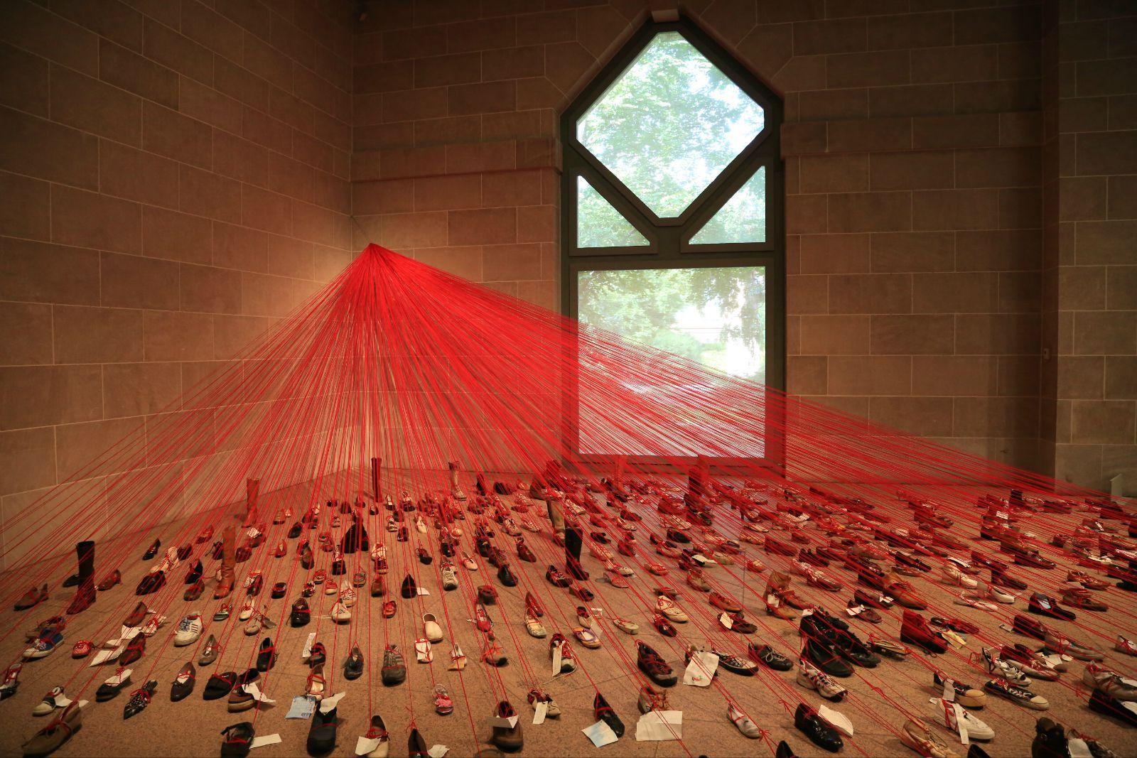 日本艺术家千春盐田的作品,收集被丢弃的鞋子绑上红线,以此来表达对过