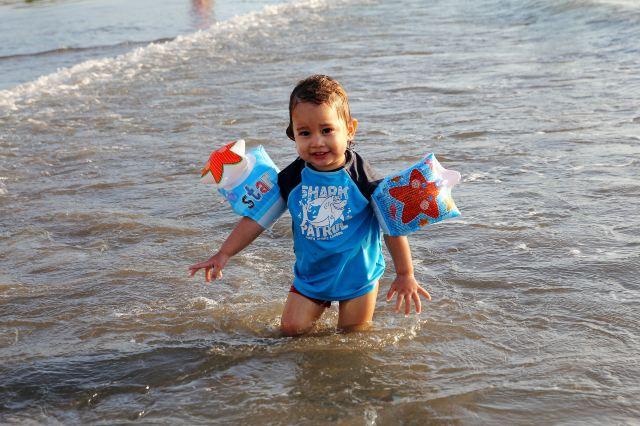 库塔海边的外国小男孩,在水里扑腾了好久