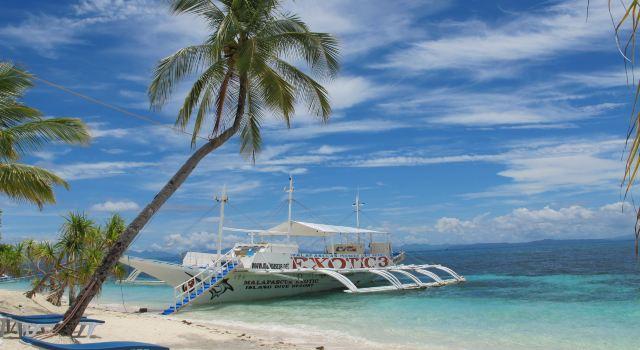 沙子细腻,门前椰子树配它家红色的船,衬上蓝天细云,拍出来的相片比