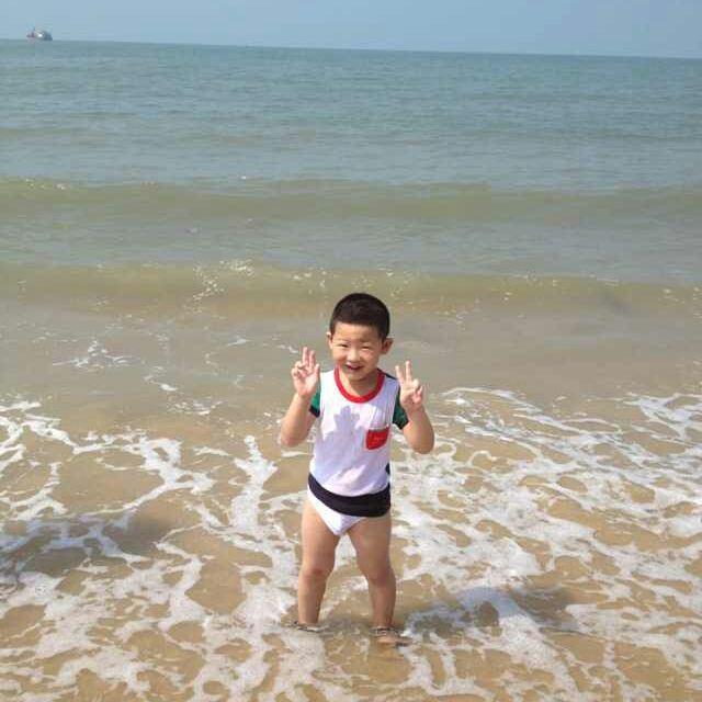小朋友在海边玩耍,不小心摔倒衣服搞湿.