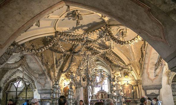 """<p class=""""inset-p"""">人骨教堂建于14世纪,其外表是看似十分普通的哥特式建筑造型,但内部的装饰却都是用人骨做成的,因此这里与其说是教堂,倒不如说是""""人骨博物馆""""。在教堂的地下室里,安放着大约4万名瘟疫死者的遗骨。</p>"""